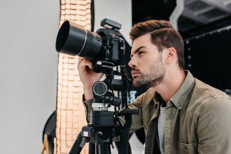 Foto de Fotógrafo profesional masculino con cámara de fotos digital en trípode en estudio fotográfico - Imagen libre de derechos