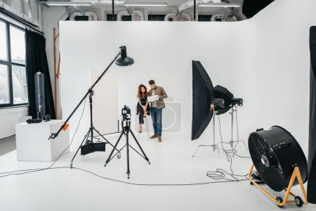Photo for Professional photographer and beautiful model with laptop in photo studio with lighting equipment - Royalty Free Image