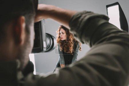 Photo pour Photographe professionnel prenant des photos avec beau modèle en studio photo avec équipement d'éclairage - image libre de droit