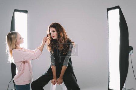 Photo pour Modèle attrayant et coiffeur dans un studio photo avec équipement d'éclairage - image libre de droit