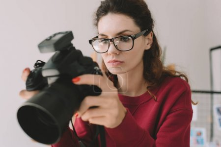 Photo for Beautiful female photographer working with digital photo camera in office - Royalty Free Image