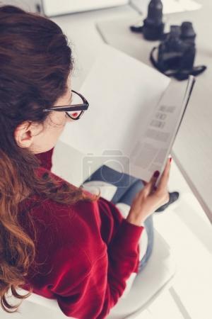 Photo pour Vue arrière du magazine de lecture de designer féminin dans le bureau moderne - image libre de droit