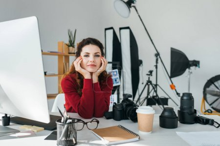attractive female photographer with lenses, photo camera and graphics tablet in modern office