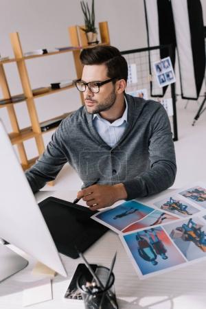 Foto de Hombre fotógrafo trabajando con ordenador, tableta gráfica y fotos en la oficina moderna - Imagen libre de derechos