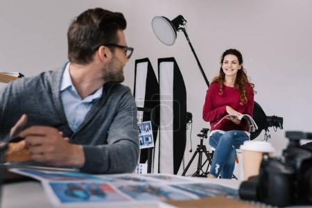 Photo pour Photographe masculin et modèle regardant l'autre dans le bureau moderne avec des photos - image libre de droit