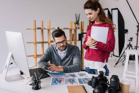 Foto de Femeninos y masculinos fotógrafos mirando fotos en la oficina moderna con ordenador - Imagen libre de derechos