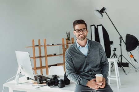 Foto de Guapo macho fotógrafo con café en la oficina moderna - Imagen libre de derechos