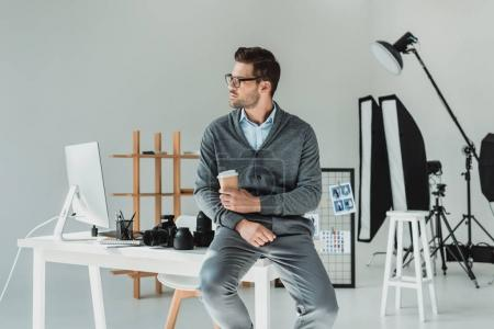 Photo for Handsome male photographer with coffee working in modern office - Royalty Free Image