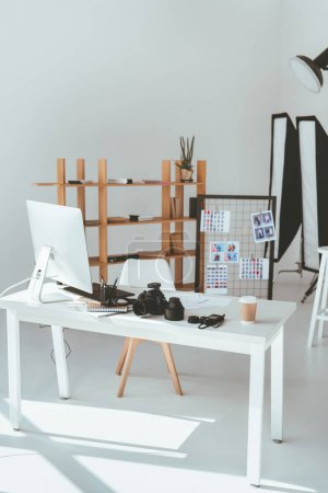Photo for Empty modern office with computer monitor, graphic tablet, photo camera and lighting equipment - Royalty Free Image