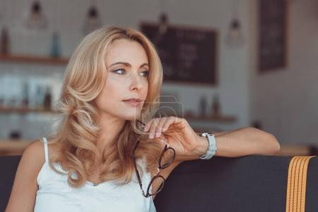 Photo for Beautiful pensive middle aged woman holding eyeglasses and looking away - Royalty Free Image