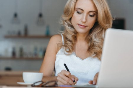 Photo for Concentrated middle aged businesswoman using laptop and taking notes in cafe - Royalty Free Image