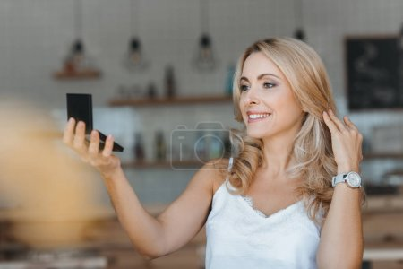 Photo for Beautiful smiling middle aged woman looking at cosmetic mirror - Royalty Free Image