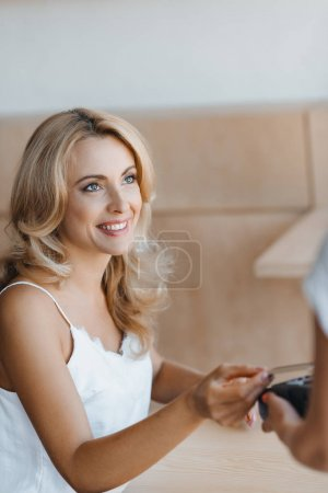 Photo for Smiling blonde woman paying by credit card and terminal in cafe - Royalty Free Image