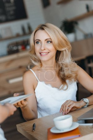 woman holding bill in cafe