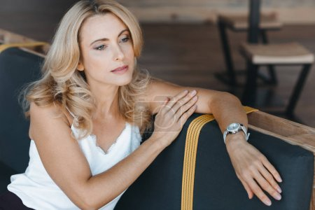 Photo for Beautiful pensive middle aged woman looking away while sitting in cafe - Royalty Free Image