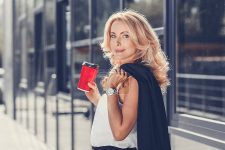 Photo for Beautiful blonde businesswoman holding disposable coffee cup and looking at camera - Royalty Free Image