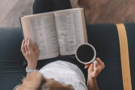 Photo pour Vue aérienne de livre de lecture de femme et boire du café dans le café - image libre de droit