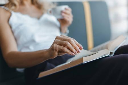 Photo pour Gros plan vue partielle de la femme lisant le livre tout en buvant du café - image libre de droit