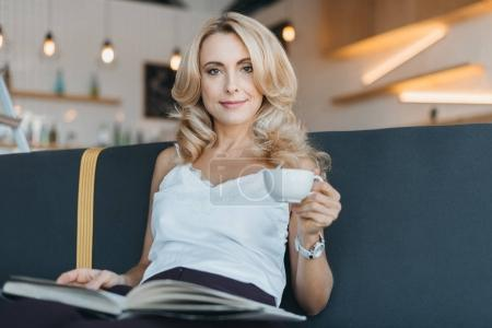Photo for Beautiful blonde mature woman reading book and drinking coffee in cafe - Royalty Free Image