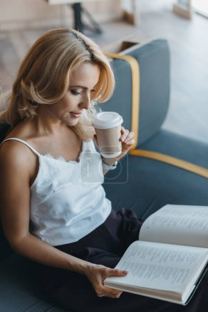 Photo for Attractive middle aged woman reading book and drinking coffee in cafe - Royalty Free Image
