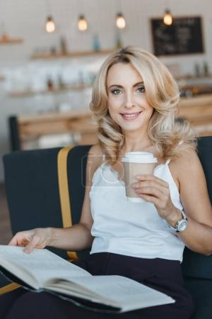 Photo for Beautiful smiling mature woman reading book and drinking coffee in cafe - Royalty Free Image
