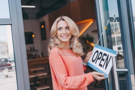 Photo for Beautiful happy cafe owner holding sign open and looking away - Royalty Free Image