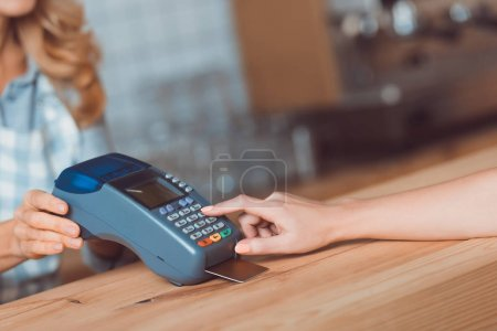 Photo for Cropped shot of customer using credit card reader in cafe - Royalty Free Image