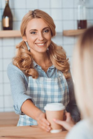 waitress holding disposable coffee cup
