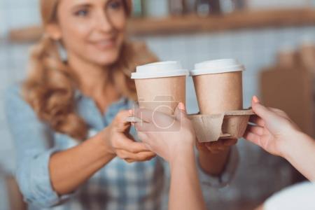 Photo pour Photo recadrée de serveuse et l'acheteur tenant café se rendre dans les gobelets en papier - image libre de droit
