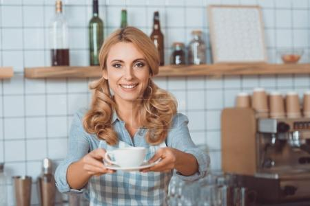 Waitress giving mug with coffee