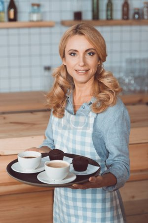 Photo for Attractive waitress in apron holding tray with cups of coffee and smiling at camera - Royalty Free Image