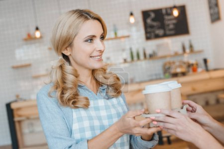 Photo for Smiling waitress in apron giving disposable coffee cups to client - Royalty Free Image