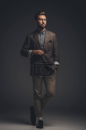Photo for Young handsome man in suit and glasses posing with hand in pocket - Royalty Free Image
