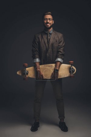 man in suit holding skateboard