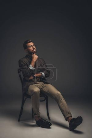 Photo for Young pensive man in suit and glasses sitting on a chair with hand on chin - Royalty Free Image