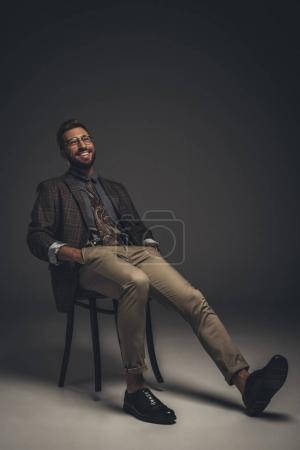 Laughing man in suit sitting on chair