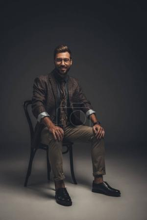 Smiling man in suit sitting on chair