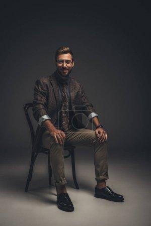Photo pour Jeune homme souriant en costume et lunettes assis sur une chaise et regardant la caméra - image libre de droit
