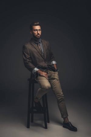 Raffinierter Mann im Anzug sitzt auf Hocker