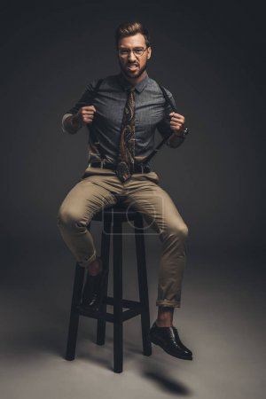 man sitting on stool and pulling suspenders