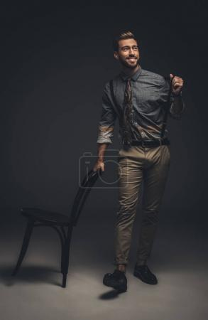 Man leaning on wooden chair
