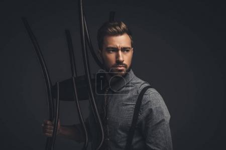 Man posing with wooden chair