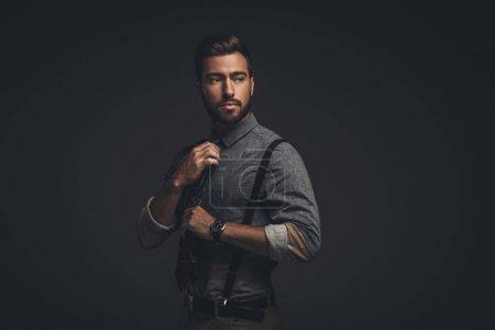 Photo pour Beau jeune homme à bretelles ajuster sa cravate - image libre de droit