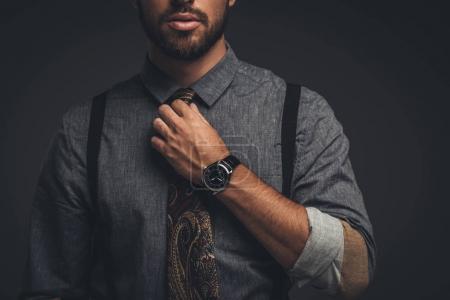 man adjusting tie