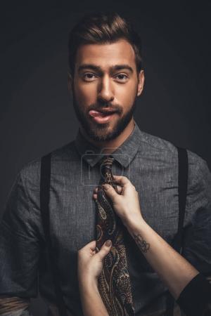 Female hands adjusting tie on man