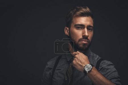 Photo pour Beau jeune homme sa barbe avec un peigne de toilettage et regardant la caméra - image libre de droit