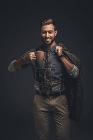 Handsome man holding cup of coffee