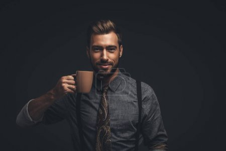 Smiling man holding cup of coffee