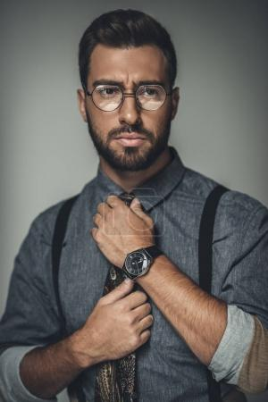 Photo for Young bearded man in glasses adjusting his tie - Royalty Free Image