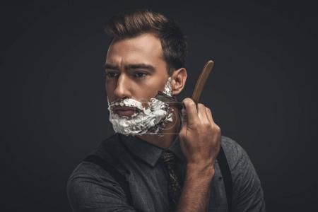 Photo for Young handsome man with shaving cream on his face, grooming his beard with straight razor - Royalty Free Image